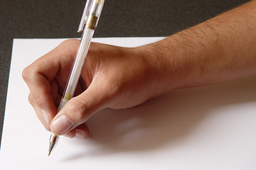 hand with pen poised to write