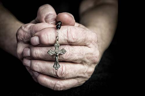 older hands holding a rosary