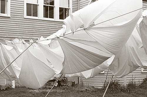 Black And White Photograph In Exhibit Showing Sheets Hung On A Clothesline Blowing In The Wind